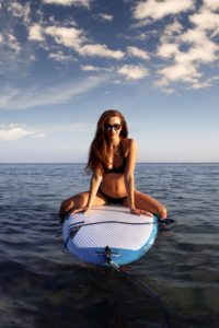 woman-sitting-on-white-surfboard-2043414